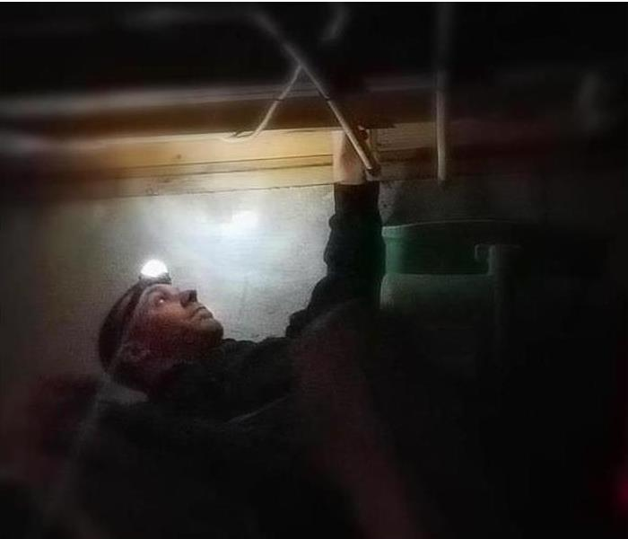 Man with flashlight looking for power